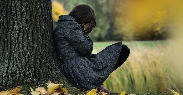 femeie sprijinita de un copac